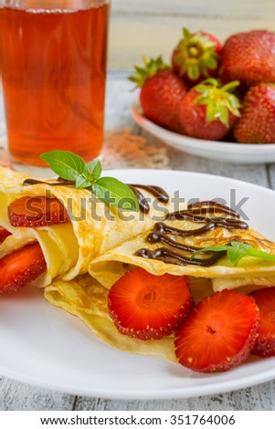 Pancakes with sliced strawberries and chocolate on the shabby wooden boards