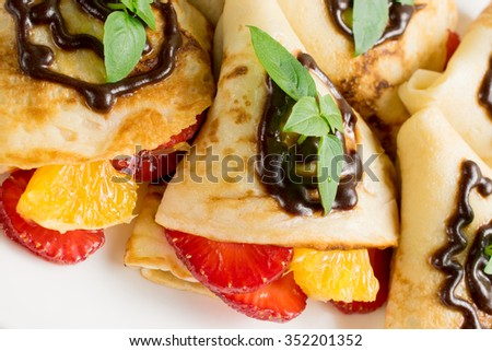 Pancakes with sliced strawberries, orange and chocolate