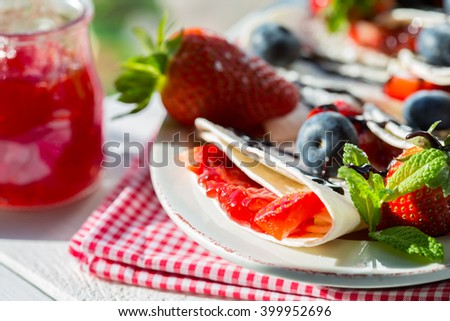Pancakes with strawberry jam and blueberries with chocolate - stock photo