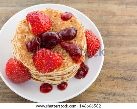 Pancakes with syrup and strawberry on white background