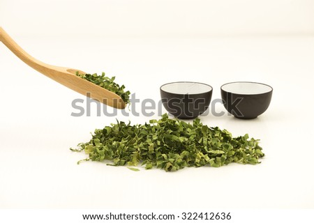 Pandan leaf tea.  Shredded pandan leaf processed and use as tea leaf for its sweet fragrance and medicinal benefits.  Straight view of bamboo spoon scoping dried leaves and two teacups at background. - stock photo