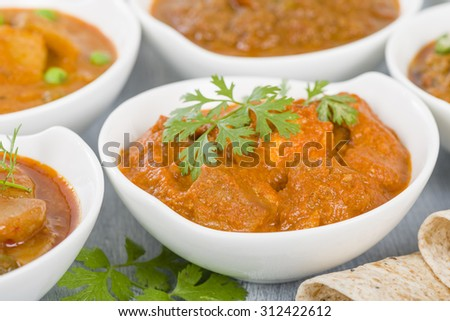 Paneer Makhani - Indian cheese cooked in a creamy sauce.  Chapattis and other vegetarian curries on background. - stock photo