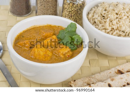 Paneer Makhani or Shahi Paneer (Paneer Butter Masala) - Indian curd cheese curry served with chapatis and pilau rice. - stock photo