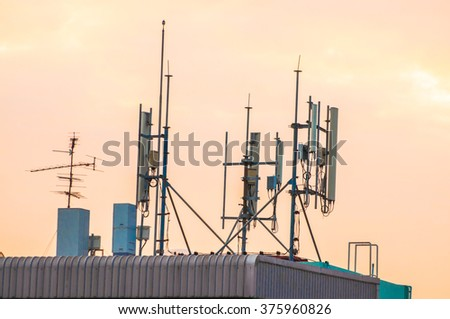 Panel antennas of cellular systems on a steel mast at the roof of building. - stock photo
