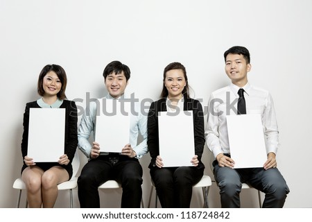 Panel of Business judges hold up blank score cards for your message. - stock photo
