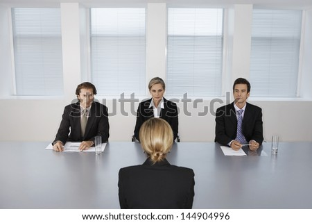 Panel of business people conducting job interview with female candidate - stock photo