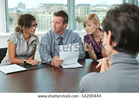 Panel of business people sitting at table in meeting room conducting job interview looking at documents. - stock photo