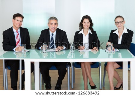 Panel of corporate personnel officers sitting at a table - stock photo