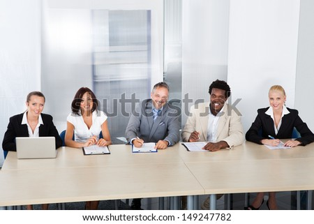 Panel Of Corporate Personnel Officers Sitting At A Table For Taking Interview - stock photo
