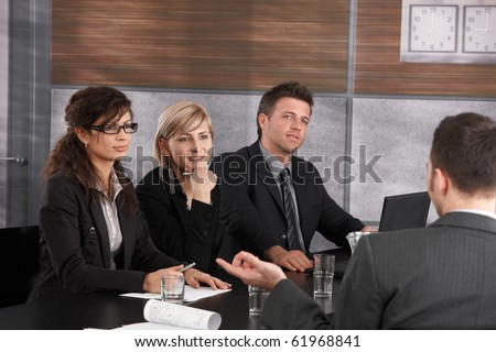 Panel of friendly businesspeople sitting at meeting table conducting job interview listening to applicant.? - stock photo