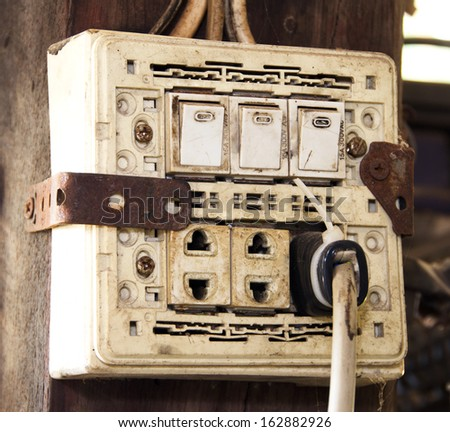 Panel switch on - off power. Socket and plug the power cord is plugged into an electrical outlet mounted on wooden poles. - stock photo