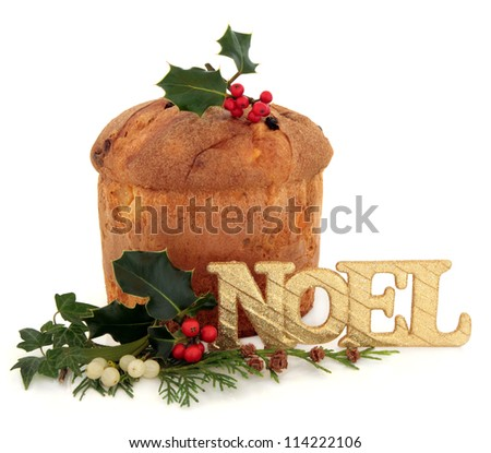 Panetone christmas cake with noel glitter sign, holly, mistletoe, ivy and cedar cypress leaf sprig decoration over white background.