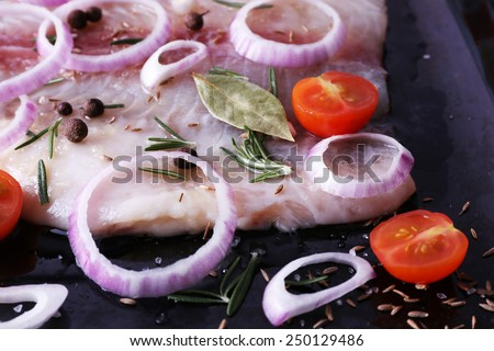 Pangasius fillet with spices and vegetables on firepan background - stock photo