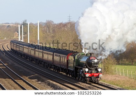 PANGBOURNE,UK - APRIL 1: Preserved steam loco Mayflower heads toward London with an early spring morning steam special passenger train on April 1, 2015 in Pangbourne