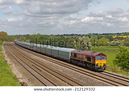 PANGBOURNE, UK - MAY 14: An EWS operated ferry wagon train passes Berkshire with a westbound freight train on May 14, 2014 in Pangbourne. EWS now owned by DBS is the largest UK rail freight operator - stock photo