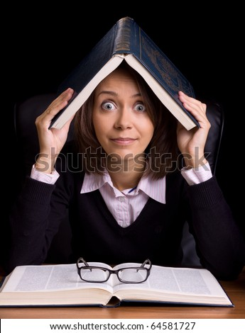 panic woman with book at the table on black background - stock photo