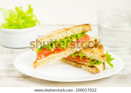 panini sandwiches with salmon, cheese and salad on a white wood background. toning. - stock photo