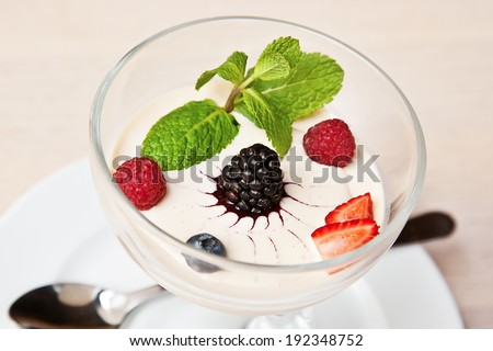 Panna cotta with bilberry, blackberry, strawberry, raspberry and mint twig