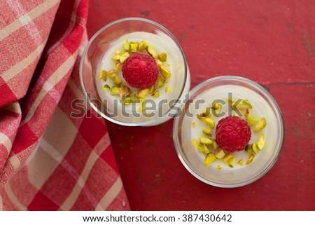 Panna cotta with raspberry and pistachio - stock photo