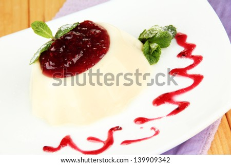 Panna Cotta with raspberry sauce, on wooden background