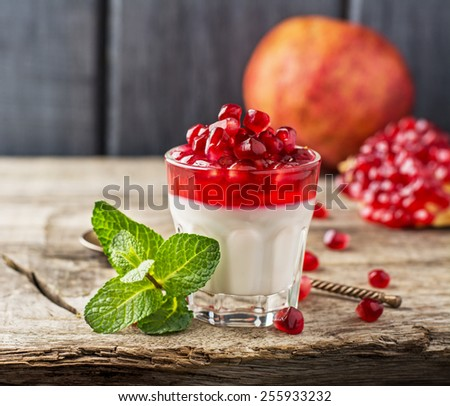 pannacotta  with pomegranate jelly and and decorated with pomegranate and mint on wooden background in glasses. selective Focus - stock photo