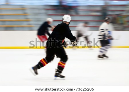 Panned motion blur of two hockey players skating down the ice rink.  Shallow depth of field. - stock photo