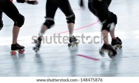 Panning action shot of skaters in a roller derby competition. Pan with motion blur. - stock photo