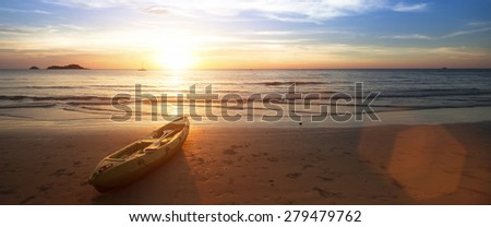 Panorama at ocean beach, canoe lying on the shore during wonderful sunset . - stock photo