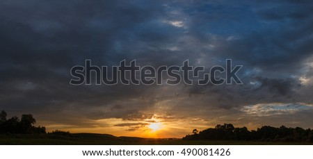 panorama beautiful cloudy sunset over green meadow, landscape