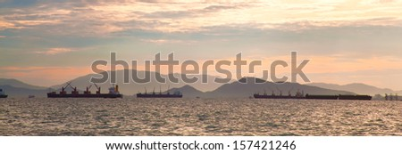 panorama cargo ship in sea at morning.background mountain in morning. - stock photo