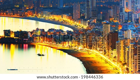 Panorama city beach at sunset with night city illumination reflected in water (Spain, Benidorm) - stock photo