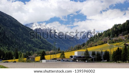 Panorama in Val d'Ultimo in South Tyrol, Italy, the valley station of a cable car, in the background the snow-capped mountains of the Ortler Group and yellow dandelion meadow / Spring in high mountains