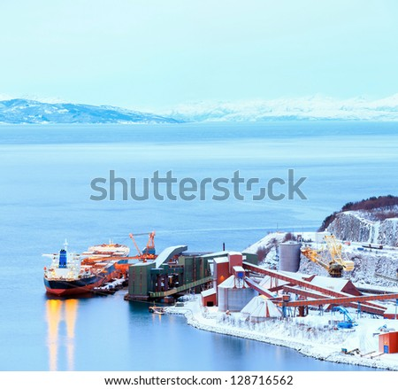 Panorama Industrial Container Cargo freight ship with working crane bridge in shipyard at Iron Ore Mine Factory Plant in Narvik Norway - stock photo
