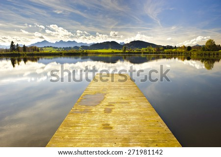 panorama landscape in Bavaria at alps mountains with lake and landing stage and mirroring - stock photo