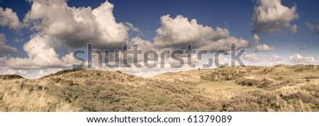 Panorama landscape of dunes under stormy sky - stock photo