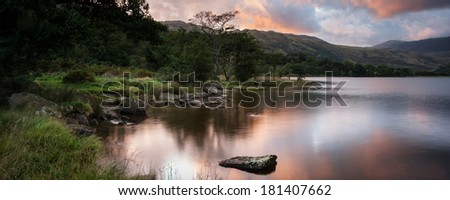 Panorama landscape stunning sunrise over lake with mountains in background - stock photo