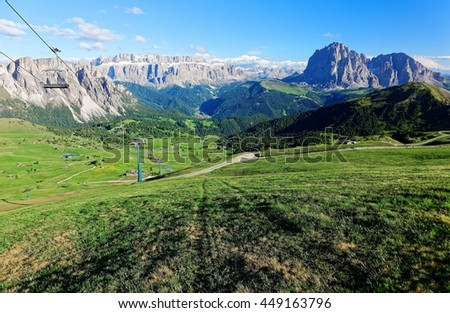 Panorama of a beautiful valley viewed from Seceda, with Mountains Stevia, Sella and Sassolungo-Sassopiatto in the background & a chairlift gliding over green meadows in Col Raiser, Dolomites, Italy - stock photo