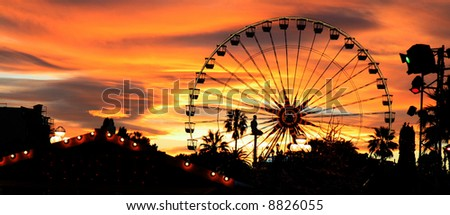 Panorama of a carnival silhouetted against the evening skyline at dusk. - stock photo