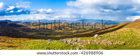 Panorama of a colourful undulating Irish landscape in Kerry with rocks in the foreground and rain and rainbow in the distance