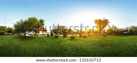 Panorama of a green garden with buddhist building and meadow with grass at early morning - stock photo