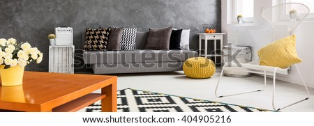 Panorama of a living room furnished in grey and white, with a wooden coffee table decorated with flowers in the foreground - stock photo