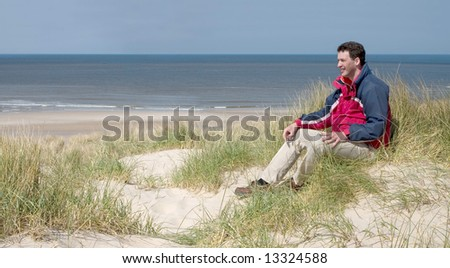 Panorama of a man sitting in the dunes (the Netherlands)