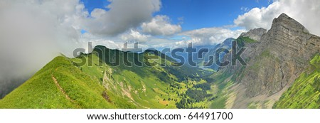 panorama of a mountain valley formed by two steep ridges with settlement and lake on the bottom in summer seen from ridge - stock photo