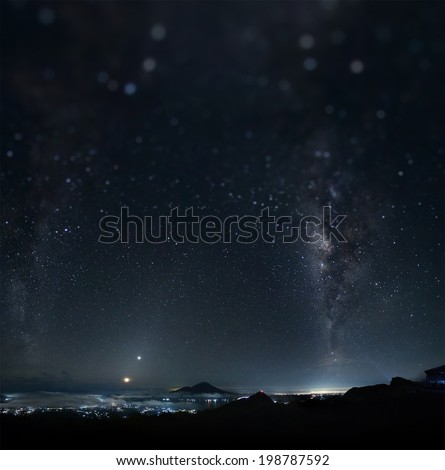 Panorama of a night sky with stars and Milky Way on equatorial latitude with mountains and illuminated town below. Tilt shift effect used - stock photo