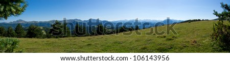 Panorama of a Pyrenees landscape with a beautiful blue sky in the background.