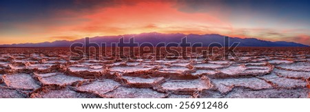 Panorama of a vivid sunset at Badwater Flat in Death Valley National Park.   The sun sets behind Telescope Peak in the background