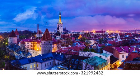 Panorama of aerial view of Tallinn Medieval Old Town with St. Olaf�¢??s Church and Tallinn City Wall illuminated in twilight, Estonia - stock photo