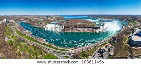 Panorama of American Falls with rainbow, Bridal Veil Falls and Horseshoe Falls,aka Canadian Falls, part of Niagara Falls on the Niagara River on the border between United States of America and Canada - stock photo