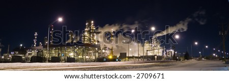 Panorama of an oil refinery at night - stock photo