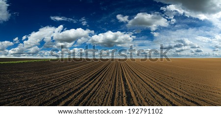 Panorama of arable land over amazing clouds - stock photo